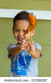 Boy happy with eating grilled chicken