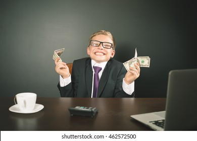 Boy has earned a lot of money. Banker holds in hand American dollars. Cunning business boy. Successful school boy. Happy. Success concept. Business suit. Stock exchange. Lucky man