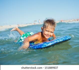 Boy has fun on the surfboard in transparency sea