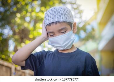 Junge hat eine Maske, um sich vor dem Corona-Virus zu schützen, muslimische kleine Junge wird krank vor Corona-Virus, Healthcares Konzept Bild von männlichen Reisenden mit einer Maske auf ihrer Nase für ihre Sicherheit Outdoor-Aktivität.