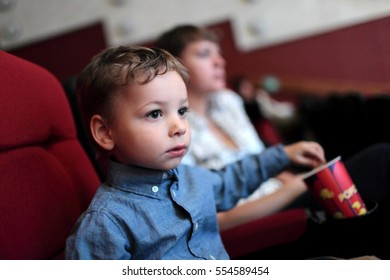 The boy has popcorn in the cinema