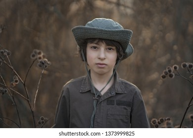 A boy in a hat and coveralls is standing in dry bushes of burdock.