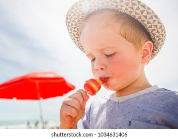 A boy in a hat eats a bright, colorful red and green ice lolly on a sunny beach with a bright red umbrella in the background.