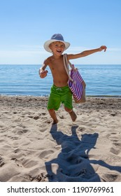 Boy in hat playing on the beach on summer holidays. Child in nature with beautiful sea, sand and blue sky. Happy kid on vacation at seaside running.