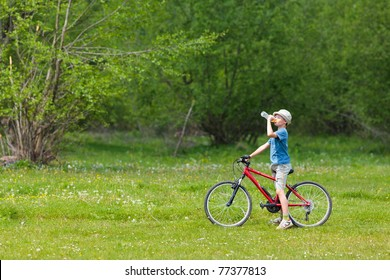 Boy with hat riding a bicycle on a grass field