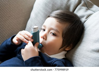 A boy have a problem with chest coughing using inhaler  for treatment , Kid using the volumtic for breathing treatment, Healthcare and medicine concept