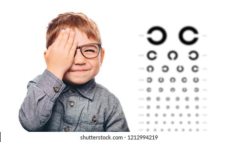 boy having eye exam with eye chart and covering one eye.