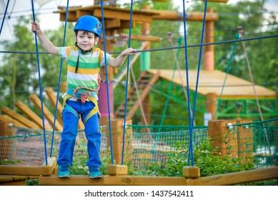 boy having fun at adventure park. toddler climbing in a rope playground structure. toddler climbing in a rope playground structure. Safe Climbing extreme sport with helmet and Carabiner