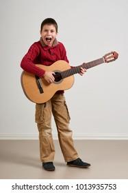Boy having fun with guitar, making music and singing
