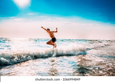 Boy Having Fun And Jumping In Sea Ocean Waves. Jump Accompanied By Water Splashes. Summer Sunny Day, Ocean Coast, Beach. Active Lifestyle And Recreation Concept.