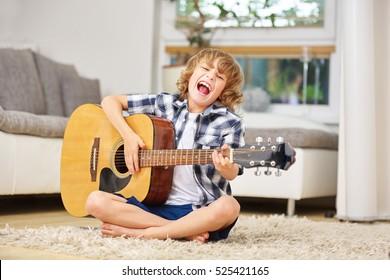 Boy having fun making music with guitar and singing along at home