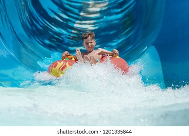 Boy having fun on the water slide on floater in the aqua fun park.