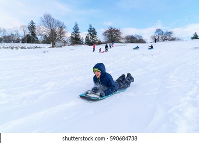 boy having fun sledding down a hill