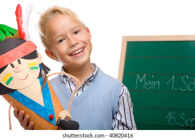 Boy having his first schoolday standing beside chalkboard