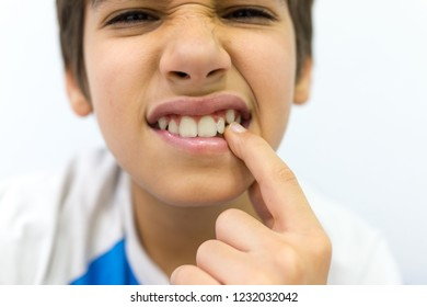 Boy having a toothache and putting his on his face
