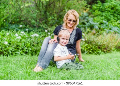 Boy in headphones having fun with mommy