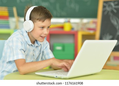 boy with headphones using laptop in classroom