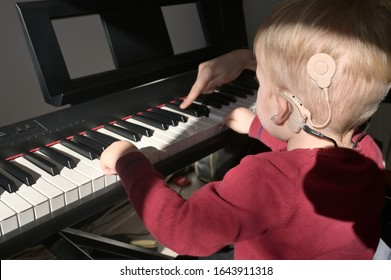 A Boy With A Hearing Aids And Cochlear Implants Playing Piano