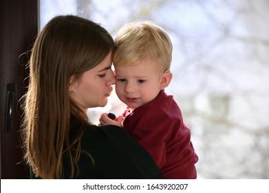 Ein Junge mit HörAIDS und Cochlear-Implantaten und seiner Mutter