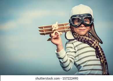 Boy in helmet and glasses with plane