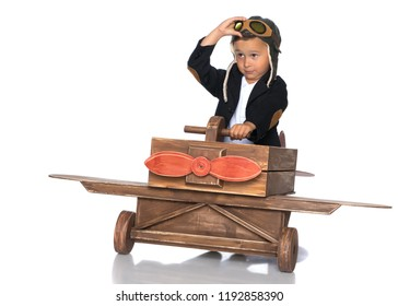 The boy in the helmet of the pilot plays with a toy wooden plane. He dreams of becoming a pilot. Concept of happy childhood, child in the family.Isolated on white background.