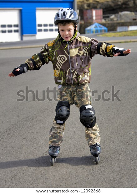 The boy in a helmet ride on roller skates