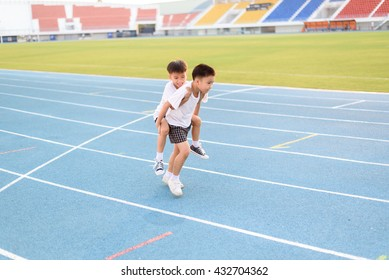 Boy help each other to run on the running track.