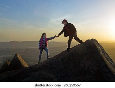 Boy helping hand girl on sunset sky background. Wichita Mountains National Wildlife Refuge