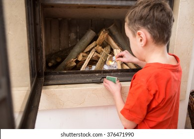 Boy helping at home, lighting the fire in the fireplace