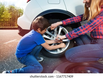 Boy helping mother to change tyre using lug wrench