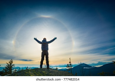 The boy hiker standing with raised hands on a top of mountain and enjoy the halo phenomenon in a sky.