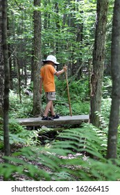 boy with hiking stick crossing a small wood bridge