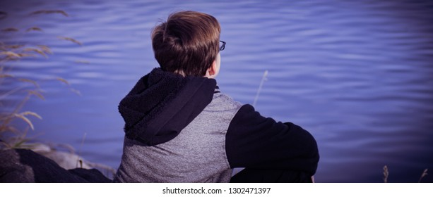 A boy with his back to the camera is in deep thought as he sits next to a peaceful beautifully colored lake.