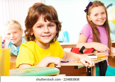 Boy and his classmates look straight, sit at desks