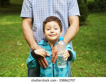 Boy with his father in the park showing water bottle to the camera.close up