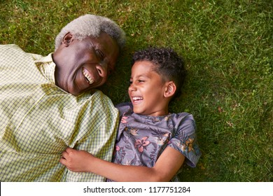 Boy and his granddad lying on grass, overhead close up
