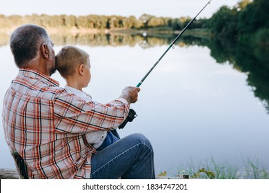 boy with his grandfather fishing on lake