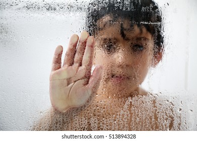 A boy with his hand pressed against a wet glass in the shower. Black and white background texture.