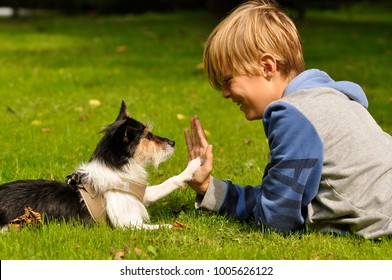 a boy and his little dog are giving themselves a high five