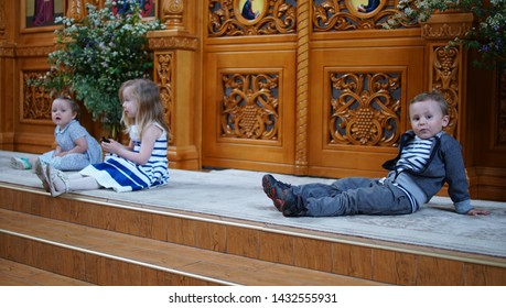 Boy and his little friend sitting on the step in the Orthodox Church, first visit and first impression in a Church.