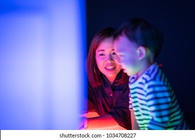 A boy and his mom are playing colorful light cubes together in the dark study room.