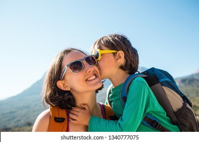The boy and his mother are sitting on the top of the mountain. A woman travels with a child. Baby kisses and hugs mom. Travel with backpacks. Hike and climb with kids. Portrait of a woman and her son.