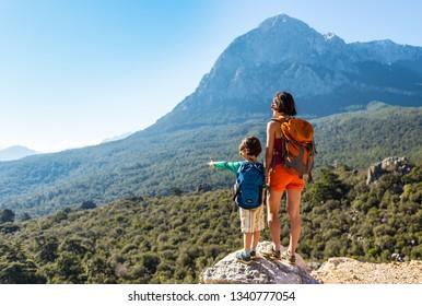 少年と彼の母親は山の頂上に立っている。女が子どもを連れて旅をしている。母親と山を見ている少年。バックパックで旅行。子どもと一緒にハイキングや登山をする。