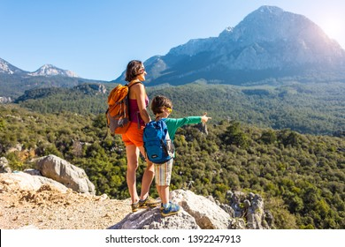 The boy and his mother are standing on the top of the mountain. A woman is traveling with child. Boy with his mother looking at the mountains. Travel with backpacks. Hike and climb with kids.