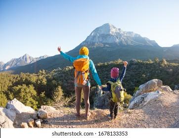 Der Junge und seine Mutter stehen auf der Bergspitze. Eine Frau reist mit einem Kind. Junge mit seiner Mutter, die die Berge betrachtet. Reisen Sie mit Rucksäcken. Wandern und klettern mit Kindern.