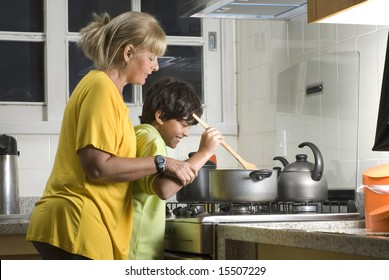 A boy and his mother are standing over the stove cooking dinner.  They are both looking at the pot.  Horizontally framed shot.