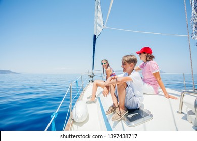 Boy with his sister and mother on board of sailing yacht on summer cruise. Travel adventure, yachting with child on family vacation.