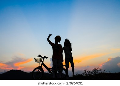 Boy with his sister riding bicycle on sunset background.Silhouette