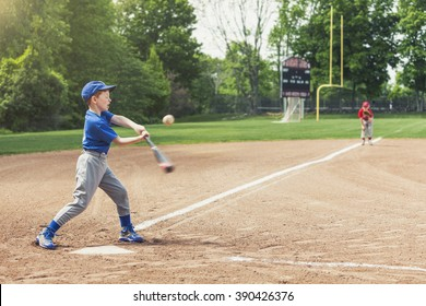 Boy hitting a baseball during a baseball game