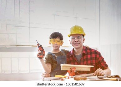A boy hold electric drill with his father who wears a helmet in workshop.father and son with drill perforating wood plank.Father teaching his son with electric drill.Happy young male carpenter. Family